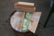 Fertig gestampftes Kraut mit anständig Saft. Als Abdeckung haben wir zuerst ein paar große Sauerkraut-Blätter obenauf gelegt, anschließend kam ein passender Holzdeckel drauf.